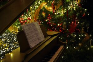 Sheet music on top of a piano which is in front of a lit Christmas tree.